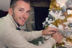 Ung blond man som dekorerar en julgran Fotografering för Bildbyråer