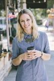 Ung blond Millennial kvinnlig med kaffekoppen royaltyfria foton