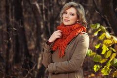 Ung blond modekvinna i beige klassiskt gå för lag som är utomhus- arkivbilder