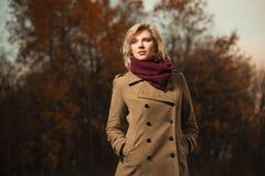 Ung blond modekvinna i klassiskt beige gå för lag som är utomhus- Royaltyfri Fotografi