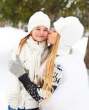 Ung blond moder som utomhus kysser hennes lilla dotter Royaltyfri Foto