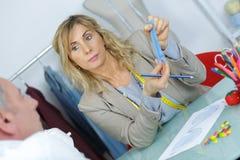 Ung blond needlewoman på studion med bandet på hals royaltyfri bild