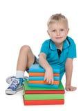 Ung blond pojke med böcker Royaltyfria Bilder