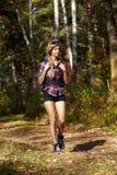 Ung blond turist- flicka med en ryggsäck i skjorta och kortslutningar Fotografering för Bildbyråer