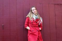 Ung blondin mot den röda väggen Arkivfoton