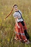 Ung bondaktig kvinna, iklädd ungersk nationell dräkt som poserar över naturbakgrund Royaltyfri Foto