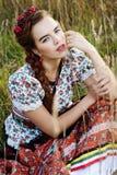 Ung bondaktig kvinna, iklädd ungersk nationell dräkt som poserar över naturbakgrund Arkivbild
