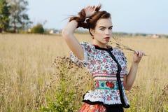 Ung bondaktig kvinna, iklädd ungersk nationell dräkt som poserar över naturbakgrund Arkivfoton