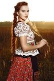 Ung bondaktig kvinna, iklädd ungersk nationell dräkt som poserar över naturbakgrund Royaltyfri Bild
