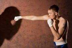 Ung boxare som stansar hans motståndare royaltyfri fotografi