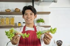 Ung bra seende man i rött förkläde som framlägger den sunda menyn av salladrulle med smil som förbereds i hem- kök arkivbilder