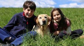 ung broder och liten syster som ler med hunden Royaltyfri Foto