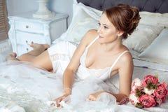 Ung brud som ligger på säng och vilar för bröllopceremoni royaltyfria bilder