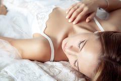 Ung brud som ligger på säng och vilar för bröllopceremoni royaltyfri fotografi