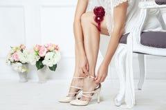 Ung brud som sätter på näcka skor arkivfoton
