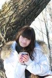 Ung brunett med en kopp te som vilar i skogen Royaltyfri Foto