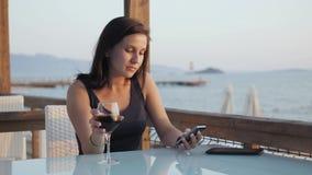 Ung brunett med exponeringsglas av rött vin genom att använda hennes Smartphone, medan sitta i kafé vid havet på solnedgången Royaltyfria Bilder