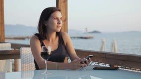 Ung brunett med exponeringsglas av rött vin genom att använda hennes Smartphone, medan sitta i kafé vid havet på solnedgången Royaltyfri Fotografi