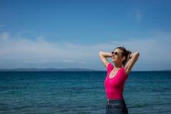 Ung brunett med färgrik solglasögon som tycker om hennes tid vid havet royaltyfri fotografi