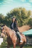 Ung brunett på en hästrygg, livsstil på bygd arkivfoto