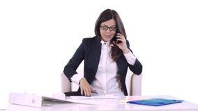 Ung brunett på vitt bakgrundssammanträde på tabellen i regeringsställning och tala på telefonen På tabellen är dokument och lager videofilmer