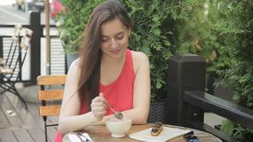 Ung brunett som dricker kaffe, medan sitta i sommarkafé lager videofilmer