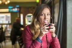 Ung brunett som dricker kaffe på en coffee shop Royaltyfri Fotografi