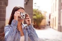 Ung brunett som fokuserar hennes gamla kamera Arkivfoton