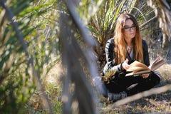 Ung brunett som läser en bok Royaltyfria Bilder