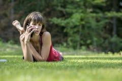 Ung brunett som ligger i grönt gräs, som hon talar på mobiltelefonen Arkivfoton