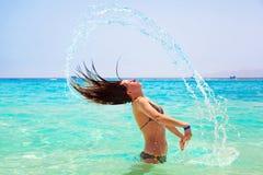 Ung brunettbanhoppning ut ur turkosvatten av Röda havet Fotografering för Bildbyråer