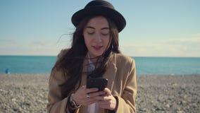 Ung brunettflicka som använder den utomhus- moderna apparaten stock video