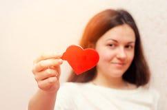 Ung brunettflicka som ger hjärta, dag för valentin` s, begrepp av förälskelse royaltyfri bild