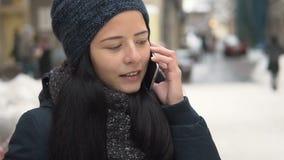 Ung brunettflicka som talar vid telefonen lager videofilmer