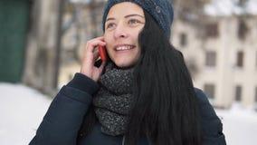 Ung brunettflicka som talar vid telefonen arkivfilmer
