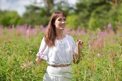 Ung brunettkvinna i den vita klänningen Royaltyfri Bild