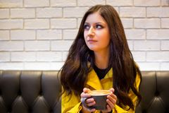 Ung brunettkvinna i en kaffehöftcoffee shop som dricker en cappuccino royaltyfri foto