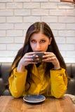 Ung brunettkvinna i en kaffehöftcoffee shop som dricker en cappuccino royaltyfri bild