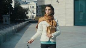 Ung brunettkvinna i exponeringsglas med böcker i händer lager videofilmer
