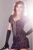 Ung brunettkvinna i svart skinande klänning Fotografering för Bildbyråer