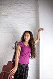 Ung brunettkvinna med den akustiska gitarren i lång kjol vägg för rastre för bakgrundstegelstenbild Royaltyfria Bilder