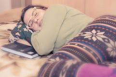Ung brunettkvinna med exponeringsglas som sover på kudden Arkivbilder