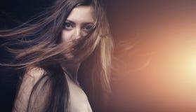 Ung brunettkvinna med långt flyghår royaltyfria foton