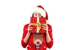 Ung brunettkvinna med långt lockigt hår som bär Santa Claus hattandd som rymmer gåvor royaltyfria foton