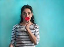 Ung brunettkvinna med röd hjärta och den randiga skjortan arkivbilder
