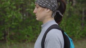 Ung brunettkvinna med ryggsäcken som går till och med le för skog stock video