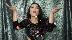 Ung brunettkvinna som blåser på konfettier lager videofilmer