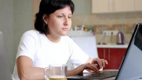 Ung brunettkvinna som dricker te från ett exponeringsglas och använder en bärbar dator lager videofilmer