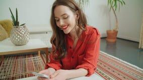 Ung brunettkvinna som hemma använder telefonen royaltyfri bild