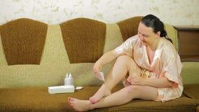 Ung brunettkvinna som hemma gör depilation av benen med vaxet och en servett arkivfilmer
